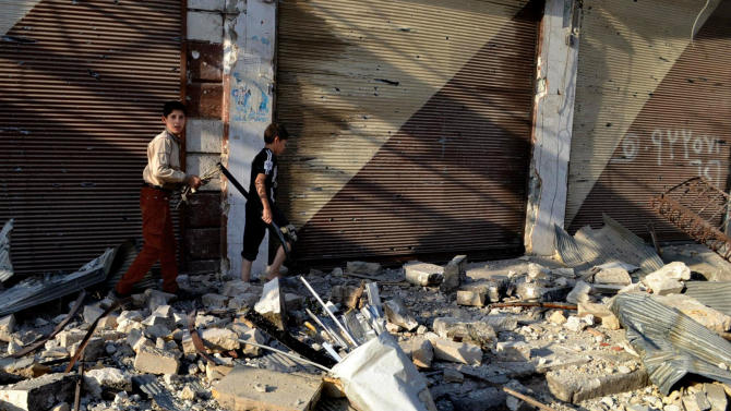 In this citizen journalism image taken on Saturday, July 28, 2012 and provided by Edlib News Network ENN, Syrian boys walk in the rubble of destroyed houses in Maarat al-Numaan on the eastern edge of Idlib province, northern Syria. (AP Photo/Edlib News Network ENN) THE ASSOCIATED PRESS IS UNABLE TO INDEPENDENTLY VERIFY THE AUTHENTICITY, CONTENT, LOCATION OR DATE OF THIS HANDOUT PHOTO