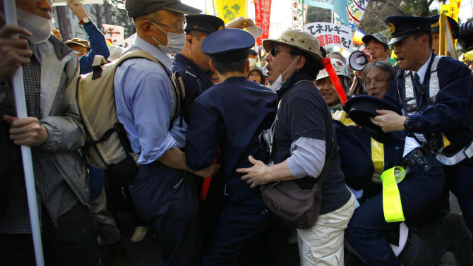 A protester scuffles with police officers during an anti-nuclear demonstration in Tokyo, Saturday, March 9, 2013. Gathering on a weekend ahead of the second anniversary of the March 11 quake and tsunami that sent Fukushima Dai-ichi plant into multiple meltdowns, demonstrators said they would never forget the world's worst nuclear catastrophe, and expressed alarm over the government's eagerness to restart reactors. (AP Photo/Junji Kurokawa)