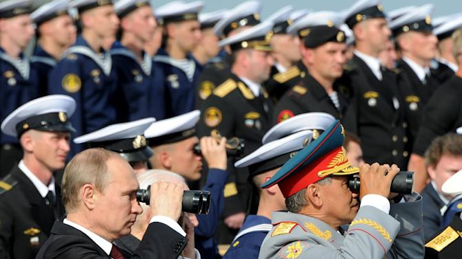 Russia's President Vladimir Putin and Defence Minister Sergei Shoigu (R) at Navy Day celebrations the in city of Severomorsk on July 27, 2014