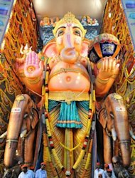 Indian devotees offer prayers to a 58-foot (17.57 meter) tall idol of the Hindu god Lord Ganesha during the Ganesh Chaturthi festival in Hyderabad. Hindu devotees bring home idols of Lord Ganesha in order to invoke his blessings for wisdom and prosperity during the 11-day celebration