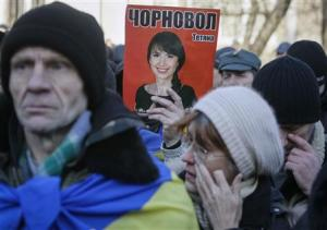 A protester holds a picture of journalist Chornovil…