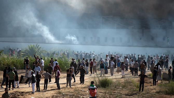 In this photo taken Friday, Sept. 14, 2012, smoke rises above protesters after they set alight cars in the U.S. embassy parking lot in Tunis. Leaked conversations in which alcohol bans and the imposition of religious law were mentioned have raised fears Tunisia's new government may not be moderate at all, especially in the context of mob attacks on the U.S. Embassy that coincided with the American ambassador's killing in neighboring Libya. (AP Photo/Amine Landoulsi)