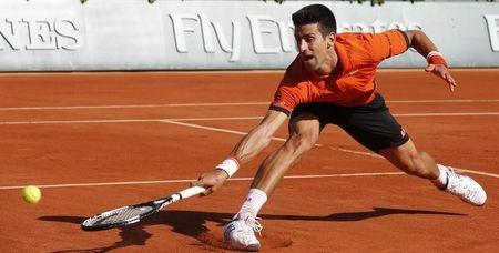 Novak Djokovic of Serbia returns the ball to Rafael Nadal of Spain during their men's quarter-final match during the French Open tennis tournament at the Roland Garros stadium in Paris