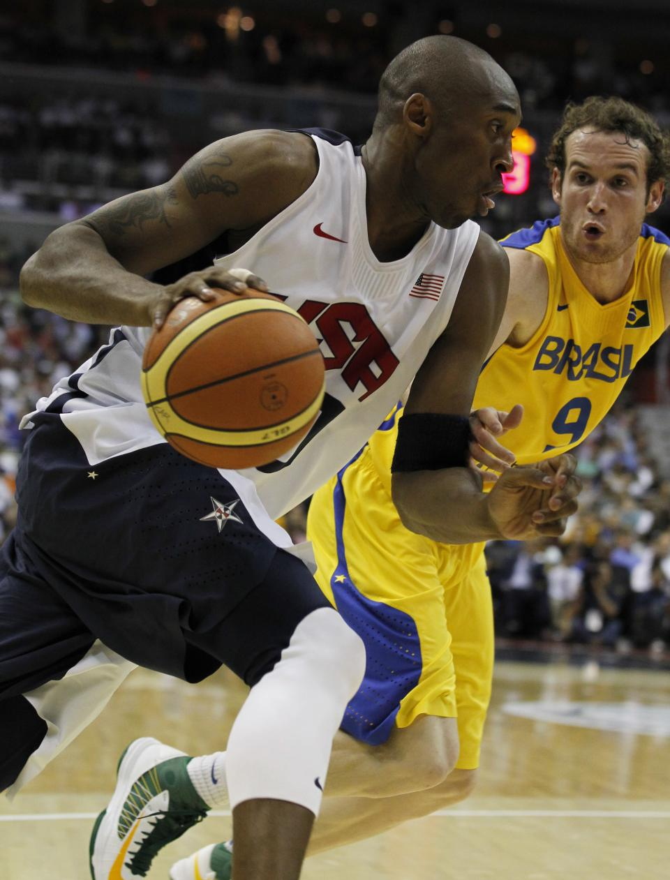 Team USA's Kobe Bryant,left, works to get past Brazil defender Marcelo Tieppo Huertas during the first half of an Olympic men's exhibition basketball game, Monday, July 16, 2012, in Washington. (AP Photo/Alex Brandon)
