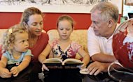 Happy Rogers (2nd R), the daughter of US investor Jim Rogers (R), reads a book while her mother Paige Parker (2nd L), younger sister Baby Bee Rogers look on, in their Singapore home in 2011. The billionaire moved his family in 2007 to Singapore after visiting Hong Kong and Shanghai in search of an ideal place to bring up his children