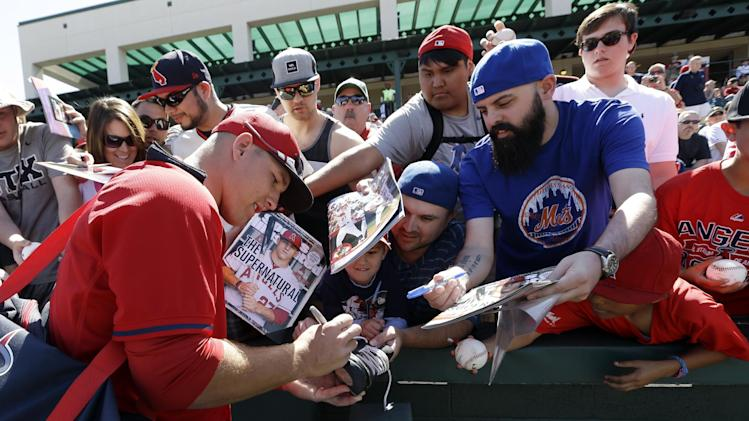 Los Angeles Angels's Mike Trout signs before an exhibition spring training baseball game against the Milwaukee Brewers Wednesday, March 12, 2014, in Tempe, Ariz. (AP Photo/Morry Gash)
