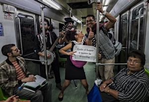 As the clowns enter the orange metro trains, some riders …