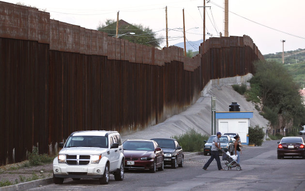 In this Aug. 9, 2012, photo, vehicles are parked along the border fence as pedestrians cross the street in Nogales, Mexico. The location is near the site where a U.S. Border Patrol agent being pelted