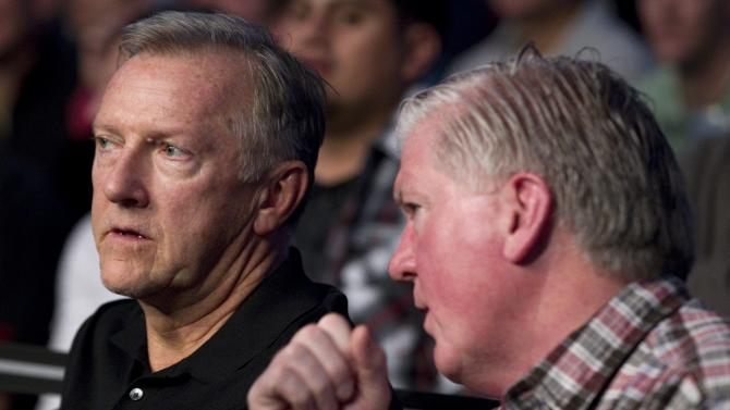 Toronto Maple Leafs general manager Brian Burke, right, and head coach Ron Wilson prepare to watch the bout between Constantinos Phillippou and Jared Hamman  during UFC 140 in Toronto, Saturday, Dec. 10, 2011. (AP Photo/The Canadian Press, Chris Young)