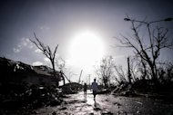 A man and a woman walk past broken trees as the sun rises in Tacloban, on the eastern island of Leyte, on November 15, 2013
