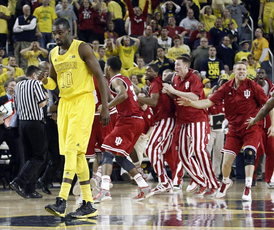 Michigan guard Tim Hardaway Jr. (10) walks off the court as Indiana celebrates a 72-71 win over Michigan in an NCAA college basketball game Sunday, March 10, 2013, in Ann Arbor, Mich. The win gave the Hoosiers their first outright Big Ten title in two decades.(AP Photo/Duane Burleson)