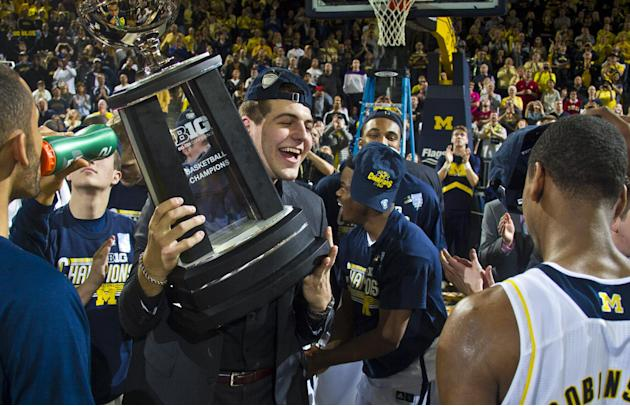 Michigan forward Mitch McGary holds the Big Ten Conference Basketball Champions trophy in celebration with teammates on the court after an NCAA college basketball game against Indiana at Crisler Cente