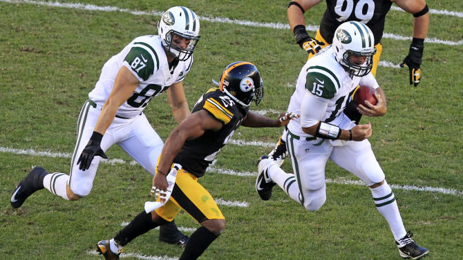 "FILE - In this Sept. 16, 2012, file photo, New York Jets quarterback Tim Tebow (15) carries the ball as Konrad Reuland (87) attempts to block Pittsburgh Steelers free safety Ryan Clark (25) during the third quarter of an NFL football game in Pittsburgh. The Jets might be down two running backs against the New England Patriots. Coach Rex Ryan says it's ""a possibility"" they could turn to do-it-all backup quarterback Tim Tebow to help out the running game Sunday.(AP Photo/Gene J. Puskar, File)"