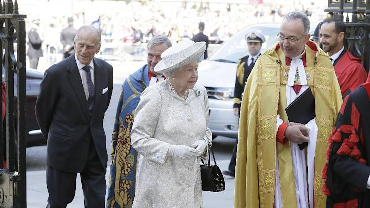 Britain's Queen Elizabeth II and her husband Prince Philip, left, arrive for service to celebrate the Queen's 60th anniversary of her coronation at Westminster Abbey, escorted by The Dean of the Abbey Dr John Hall in London, Tuesday, June 4, 2013. (AP Photo/Alastair Grant)
