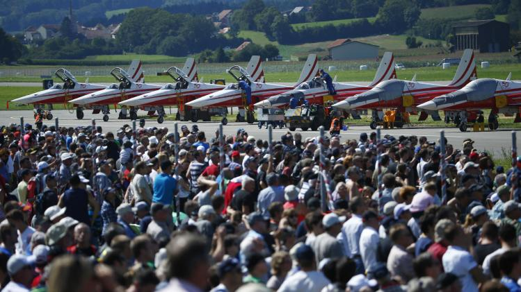 Spectators stand in front of Swiss Air Force aerobatics team Patrouille Suisse and their F-5E Tiger II aircrafts during the Air14 airshow in Payerne