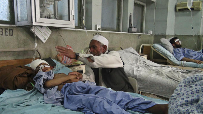 An Afghan man sits near his wounded grandson, due to a 5.7 magnitude earthquake, in a hospital in Jalalabad, Afghanistan, Wednesday, April 24, 2013. An earthquake struck the northeast and neighboring Pakistan on Wednesday, which left several people dead and many injured, officials said. (AP Photo/Babrak Amirzada)