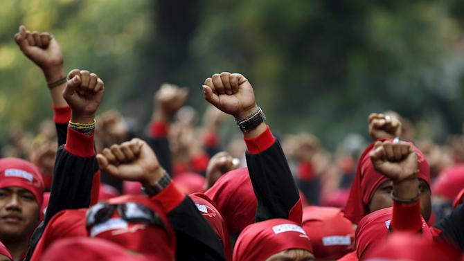 Indonesian trade union supporters march towards the Presidential Palace in Jakarta