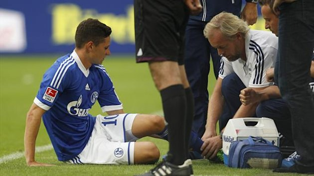 A doctor looks at an injury of Schalke 04's Julian Draxler (L) during the German first division Bundesliga soccer match against Hamburg SV in Gelsenkirchen August 11, 2013 (Reuters)