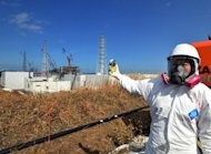 This file picture taken on February 28, 2012 shows a journalist checking radiation levels near the TEPCO Fukushima Dai-ichi nuclear power plant in Fukushima prefecture, northern Japan. Japan on Friday insisted warnings by the World Health Organisation of a rise in the risk of cancer for people in Fukushima were overblown, saying the agency was unnecessarily stoking fears