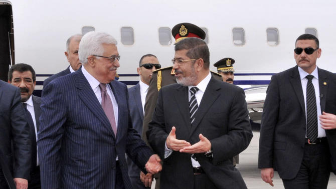 In this photo released by the Egyptian Presidency, Palestinian President Mahmoud Abbas, second left, walks with Egyptian President Mohammed Morsi, center, following Abbas' arrival in Cairo, Egypt, for the Organization of Islamic Cooperation summit, Tuesday, Feb. 5, 2013. (AP Photo/Egyptian Presidency)