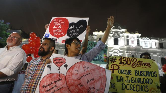 Members of gay and lesbian organizations hold signs as they march in support of the Civil Union project law in Lima