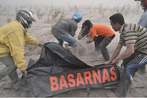 Indonesian rescuers recover the body of a victim at a village in Karo district following eruptions of Mount Sinabung, on Sumatra island, on February 1, 2014