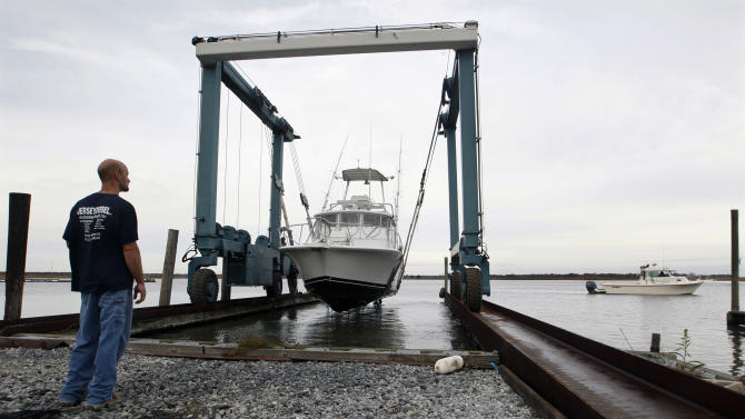 Another boat waits its turn, as manager Scott Buck watches as a 50-ton lift raises a fishing boat out of the Maurice River at Yank Marine Services marina Saturday, Oct. 27, 2012, in Dorchester, N.J., in preparation for Hurricane Sandy. From the lowest lying areas of the Jersey Shore, where residents were already being encouraged to leave, to the state's northern highlands, where sandbags were being filled and cars moved into parking lots on high ground, New Jersey began preparing in earnest for Sandy. (AP Photo/Mel Evans)
