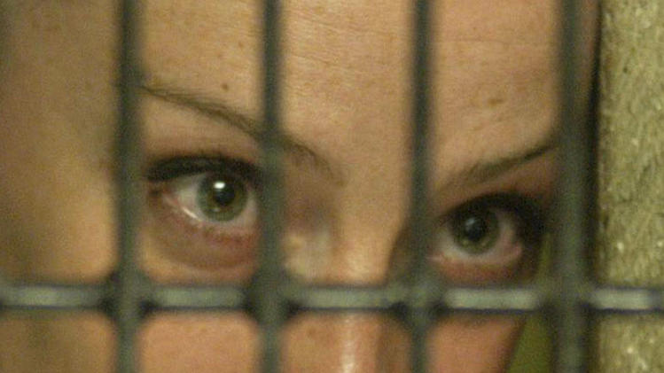 FILE - In this Dec. 2005 file photo, French citizen Florence Cassez looks out from behind bars at a federal prison in Mexico City.  A Mexican Supreme Court panel voted Wednesday, Jan. 23, 2013,  to release Cassez, who was sentenced to 60 years in prison for kidnapping. Cassez was arrested in 2005 and convicted of helping her Mexican then-boyfriend run a kidnap gang. The five-justice panel voted 3-2 to order Cassez released because of procedural and rights violations during her arrest. (AP Photo, File)