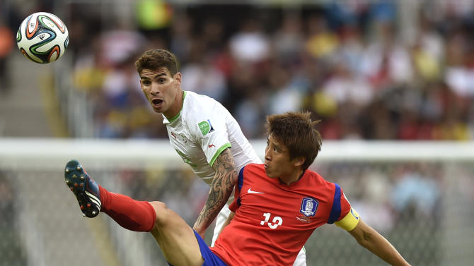 South Korea's Koo Ja-cheol , front, reaches to the ball ahead of Algeria's Carl Medjani during the group H World Cup soccer match between South Korea and Algeria at the Estadio Beira-Rio in Porto Alegre, Brazil, Sunday, June 22, 2014. (AP Photo/Martin Meissner)