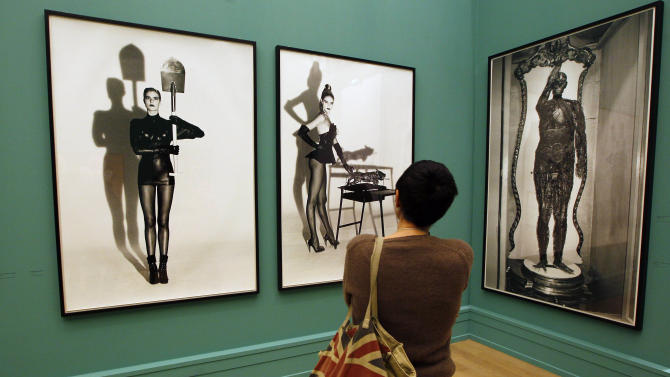 A visitor looks at the work of late fashion photographer Helmut Newton at the opening of his first retrospective in France at Paris' Grand Palais museum, Friday, March 23, 2012. The exhibit, curated by his widow June Newton, contains some 250 pictures, many of which are provocative and erotically charged. His black-and-white photos were a mainstay of fashion magazines across the world for several decades, especially Vogue Paris. (AP Photo/Francois Mori)