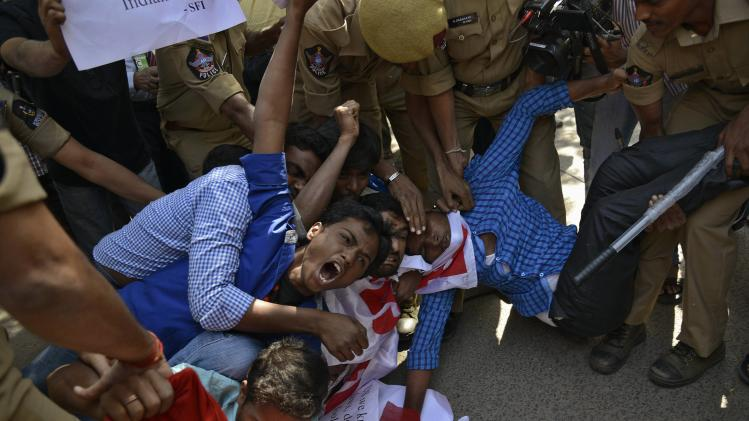 Members of SFI shout slogans as policemen try to detain them during a protest outside the U.S. consulate office in Hyderabad