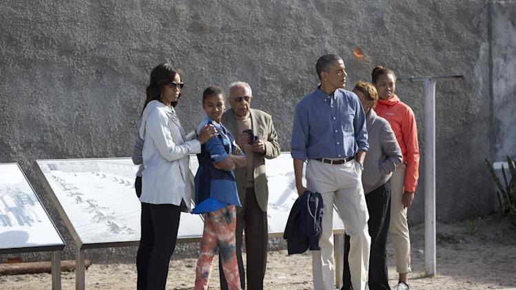 From left, first lady Michelle Obama, Sasha Obama, Ahmed Kathrada former prisoner with Nelson Mandela guiding the tour, U.S. President Back Obama, Marian Robinson and Leslie Robinson, look out over the courtyard of the prison on Robben Island, South Africa, Sunday, June 30, 2013. Former South African president Nelson Mandela spent 18 years of his 27-year prison term on the island locked up by the former apartheid government. (AP Photo/Carolyn Kaster)