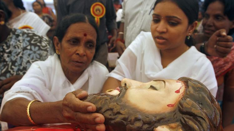 A Catholic devotee touches a statue of Jesus Christ to get blessings during Good Friday prayers at a church in Chennai