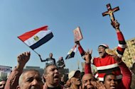 A man holding a cross and a Koran takes part in a demonstration in Cairo's Tahrir Square, on February 8, 2013. Shortly after Muslim noon prayers, marchers set off from several locations in Cairo to Tahrir Square and the presidential palace, banging on drums, waving flags and clapping in unison