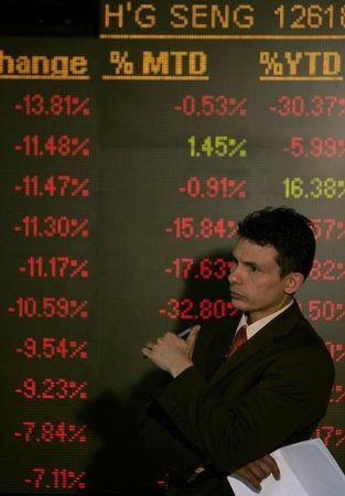 A man stands next to a digital board at the Johannesburg Stock Exchange in Sandton