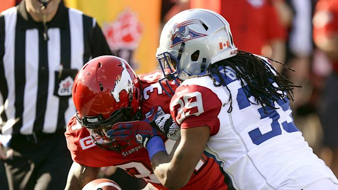 Calgary Stampeders' Harrison is hit by Montreal Alouettes' Brown during their CFL football game in Calgary