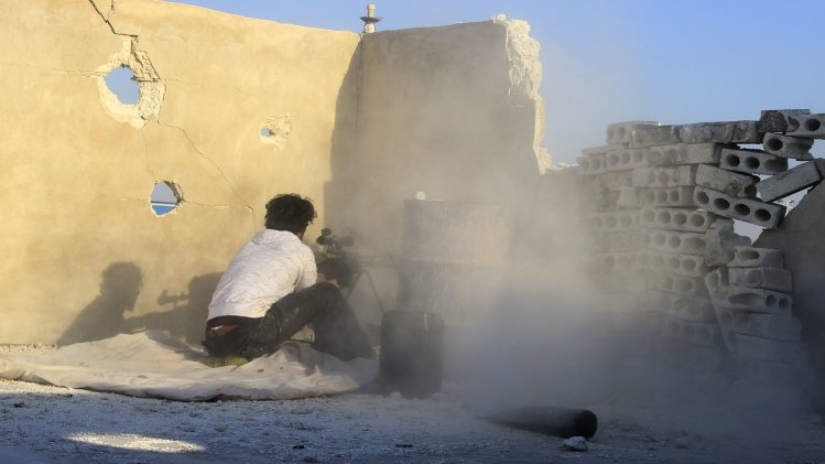 Free Syrian Army fighter fires as he takes a defensive position in Aleppo's Sheikh Saeed neighbourhood