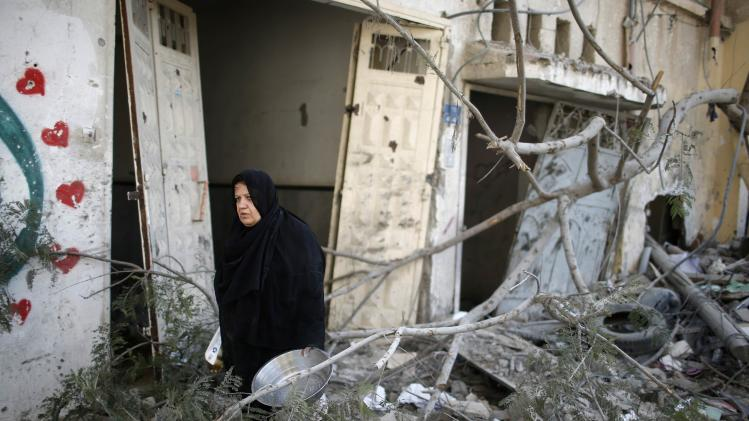 A Palestinian woman carries her belongings from her damaged house in the Shejaia neighborhood east of Gaza City
