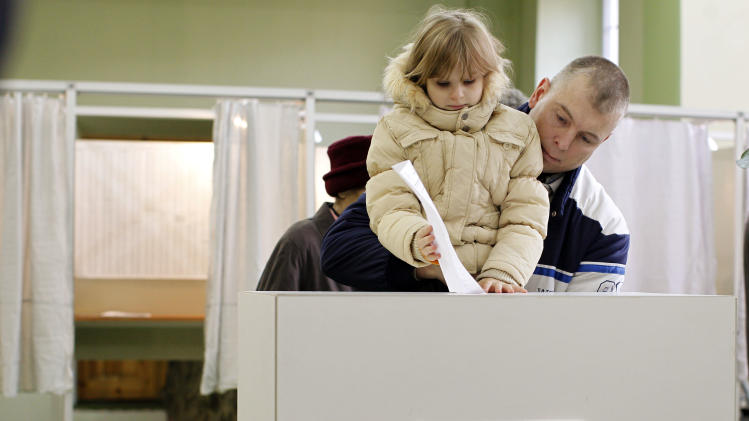 A man with a child casts his ballot at a polling station in  Vilnius, Lithuania, Sunday, Oct. 14, 2012. Lithuanians are expected to deal a double-blow to the incumbent conservative government in national elections Sunday by handing a victory to opposition leftists and populists and saying 'no' to a new nuclear power plant that supporters claim would boost the country's energy independence. (AP Photo/Mindaugas Kulbis)