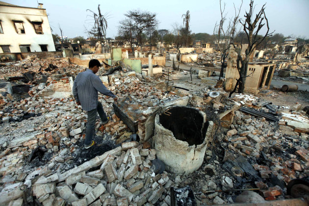 A man walks among debris of buildings destroyed during ethnic unrest between Buddhists and Muslim in Meikhtila, about 550 kilometers (340 miles) north of Yangon, Myanmar, Monday, March 25, 2013. Secta