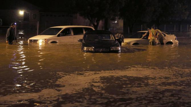Firefighters arrive to rescue stranded motorists as heavy rains caused flash flooding, stranding cars Tuesday, Aug. 12, 2014, in Laveen, Ariz. Authorities say at least six people have been rescued from vehicles that were stuck in flooded streets in Phoenix. (AP Photo/Ross D. Franklin)