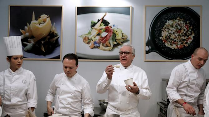 Chef Alain Ducasse poses with his kitchen brigade during the Taste of Paris festival at the Grand Palais in Paris