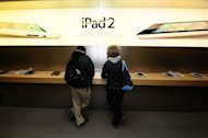 <p>Customers try the iPad 2 at the Apple store on Fifth Avenue in New York in 2011. Apple stock price leaped to a new high on Friday amid rumors it is poised to hit the market with new versions of iPhone, iPad, and Apple TV devices.</p>