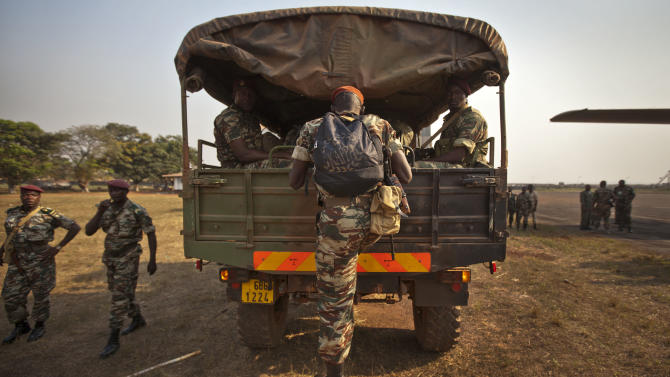 A soldier jumps onto his truck as it departs, after the final contingent of reinforcements under current deployment plans, a group of around forty soldiers from Cameroon, arrived to bolster the multinational central-african regional force known as FOMAC which now numbers around a thousand troops, at the airport in Bangui, Central African Republic Thursday, Jan. 3, 2013. Facing an insurgency by a new rebel coalition, Central African Republic President Bozize consolidated military power under his control Thursday after dismissing his own son as acting defense minister along with his army chief of staff. (AP Photo/Ben Curtis)