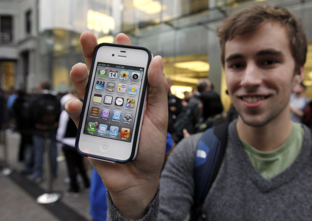 FILE - In this Oct. 14, 2011 file photo, Elliott Johns, of Boston, holds up an iPhone 4S in front of an Apple Store location in Boston. Apple Inc., the world's most valuable company, on Tuesday, April 24, 2012 trumped skeptics once again by reporting blow-out iPhone sales. Apple says it sold 35 million iPhones in the quarter, almost twice as many as it sold a year ago and above analyst expectations. (AP Photo/Steven Senne, File)