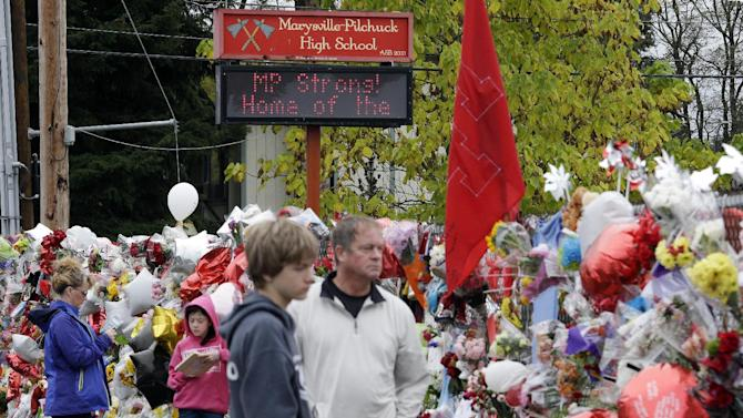 File- This Oct. 30, 2014, file photo shows Gay Soriano, left, talking with daughter Gabby, 11, as her brother Titan, 13, and father Rick walk nearby and along a memorial for victims of a deadly school shooting nearly a week earlier, in Marysville, Wash. One of the teenagers wounded in a Washington state high school shooting died Friday, raising to four the number of fatalities from the moment when a student opened fire in a cafeteria a week ago. Shaylee Chuckulnaskit, 14, died late Friday, Oct. 31, 2014, officials at Providence Regional Medical Center in Everett said. (AP Photo/Elaine Thompson, File)