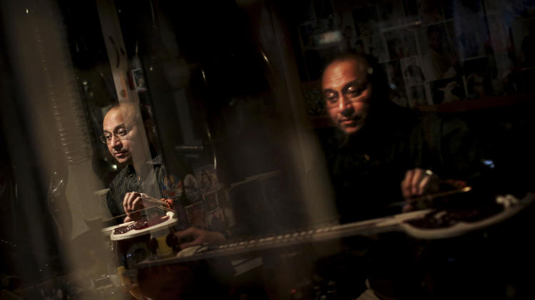 "Indian traditional instrument craftsman Sanjay Sharma places a fret on a sitar at his store Riki Ram's Music in New Delhi, India, Thursday, Dec. 13, 2012. For close to a 100 years Sharma's family has created musical instruments for legendary Indian musicians. But none more famous than sitar virtuoso Ravi Shankar who died Tuesday at age 92. Described as ""the godfather of world music"" by Beatle George Harrison, Shankar introduced millions of Westerners to the sitar and the centuries-old traditions of Indian classical music. (AP Photo/Kevin Frayer)"