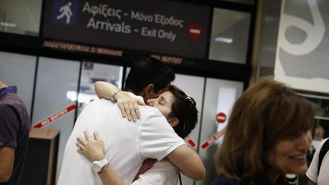 A woman evacuated from Libya is hugged by a man after arriving at a port of Piraeus, near Athens, Greece, on Saturday, Aug. 2, 2014. A Greek navy frigate carrying embassy staff and nearly 200 people from Greece, China and other countries evacuated from the conflict in Libya returned early Saturday to the port. The Greek Defense Ministry the ship transported 77 people from Greece, 78 from China, 10 from Britain, seven from Belgium, one each from Russia and Albania. (AP Photo/Petros Giannakouris)