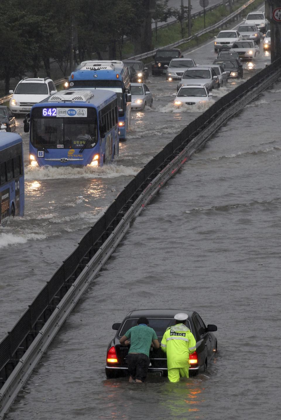 A driver and a police officer push a stalled car on a submerged road in Seoul, South Korea, Wednesday, July 27, 2011. A quick blast of heavy rain sent landslides barreling through South Korea's capital and a northern town Wednesday. (AP Photo/Yonhap)  KOREA OUT