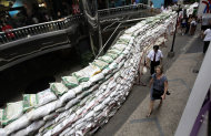 A foreign tourist walks past a shopping mall fortified with sandbags in Bangkok, Thailand, Friday, Nov. 11, 2011. Thailand is once again in tourist turmoil as floods linger, but ever resilient industry unfazed. (AP Photo/Altaf Qadri)